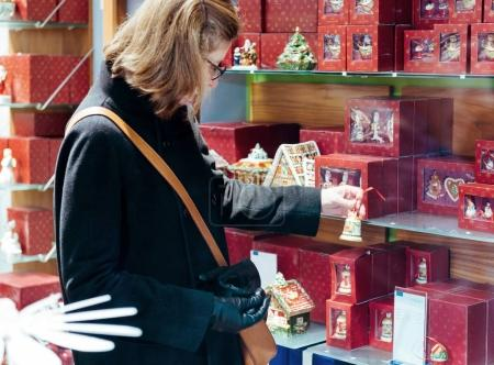 French elegant woman search for the Christmas gift in shop from the French Street - searching for the best present during Christmas holidays