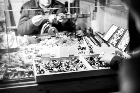 Unrecognizable glass blower preparing traditional Christmas toys souvenirs at the Christmas Market