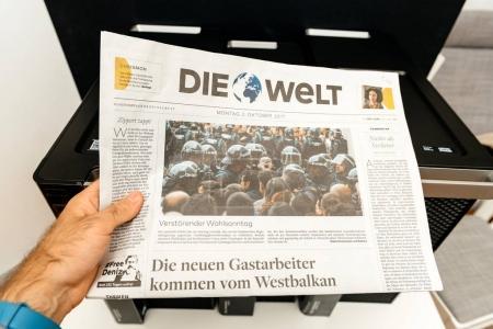 Man reading Die Welt German newspaper