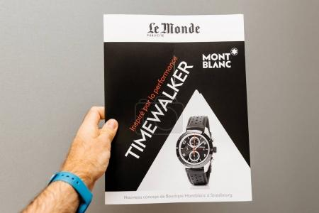 Man holding against gray background a Le Monde newspaper supplem