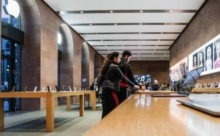 ouple inside Apple Store deciding to buy latest MacBook Pro