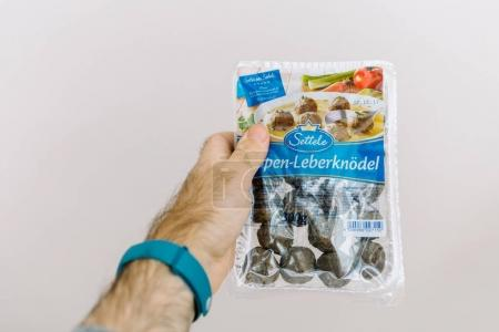 PARIS, FRANCE - September 25, 2017: Man hand holding against white background package of Meatballs Sopen-Leberknodel by Settele