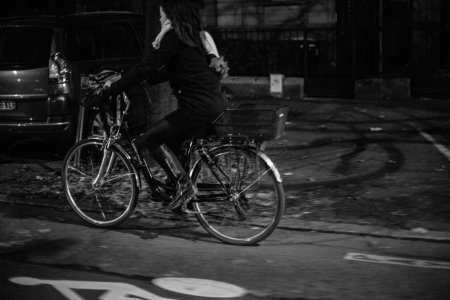 STRASBOURG, FRANCE - September 31, 2017: Woman commuting on bike in French city at night - black and white image