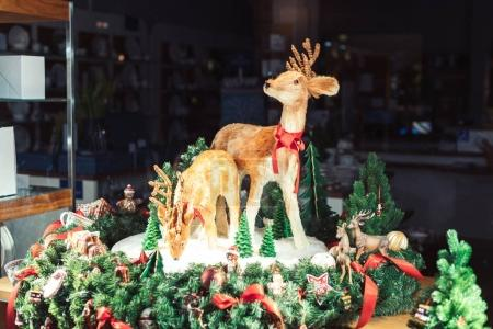 Two reindeers surrounded with Christmas decorations during winter holiday
