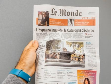 LYON, FRANCE - April 10, 2017: Man holding le monde french newspaper POV with international news from Spain to France and USA