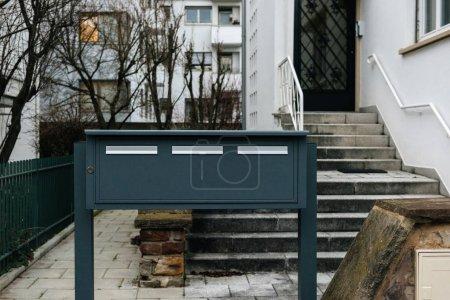 Photo pour Trois boîtes aux lettres grises devant la façade moderne de la maison en France - image libre de droit