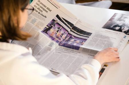 Woman Reading Le Monde newspaper with French presidential debate