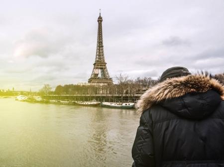 Photo pour Vue arrière d'un vieil homme parisien méconnaissable observant la Seine gonflée près de la Tour Eiffel alors que les berges débordent après des jours de fortes pluies. - image libre de droit