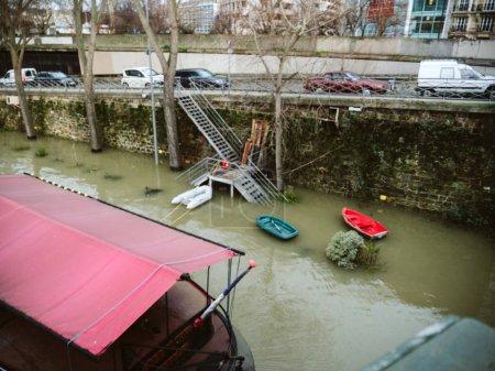 Photo pour Vue déconcentrée de la rivière gonflée Les remblais de la Seine débordent après des jours de fortes pluies - bateaux utilisés pour les personnes vivant sur les péniches - image libre de droit