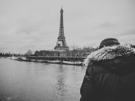 Photo pour Un aîné parisien méconnaissable observe la Seine gonflée près de la Tour Eiffel alors que les berges débordent - image libre de droit