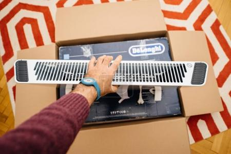 Man unboxing heating convecter DeLonghi from Amazon