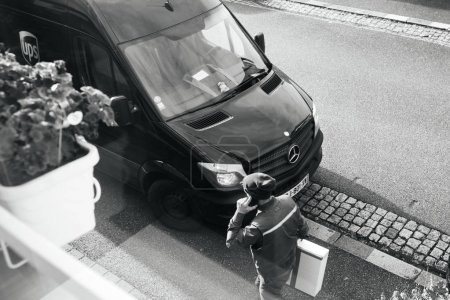 Photo for PARIS, FRANCE - FEB 16, 2018: Courier enters UPS United PArcel Service brown delivery van with cardboard parcel in the hands delivering the on time delivering package parcel - view from above black - Royalty Free Image