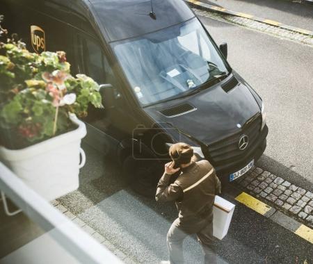 Photo pour Paris, France - 16 février 2018: Courier saisit van brun Livraison Ups United Parcel Service avec carton colis dans les mains offrant le temps sur livraison colis paquet - vue d'en haut - image libre de droit