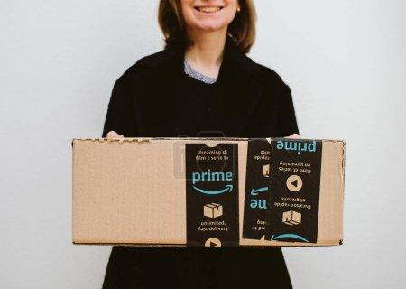 Smiling woman holding Amazon Prime parcel cardboard box