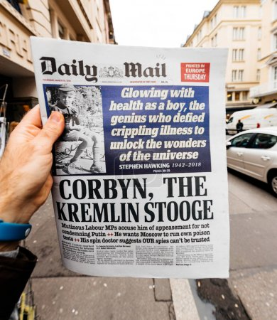 Male hand holding British Daily Mail newspaper with portrait of