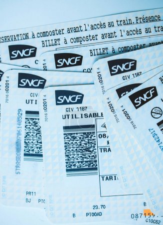 Photo for PARIS, FRANCE - JAN 14, 2015: Stack of multiple SNCF Societe nationale des chemins de fer francais train tickets seen from above randomly arranged on a table blue tint - Royalty Free Image