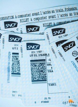 Photo pour Paris, France - 14 janvier 2015: Pile de multiples Sncf Societe nationale des chemins de fer francais billets vus d'en haut, au hasard de train disposées sur une teinte de table bleu - image libre de droit