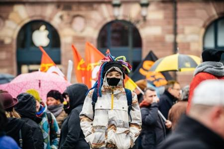 Photo for STRASBOURG, FRANCE  - MAR 22, 2018: Young boy with funny hat and mask at demonstration protest strike against Macron French government string of reforms - defocused crowd background - Royalty Free Image