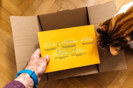 Man unboxing Amazon.com cardboard containing a surprise envelope