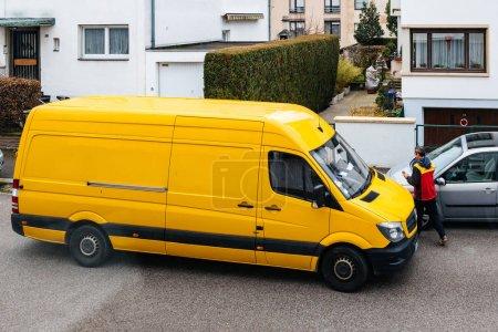 Photo pour Paris, France - 30 mars 2018: Courier pénètre dans Dhl jaune camionnette après avoir prononcé le temps sur livraison colis paquet dans quartier européen typique - vue - image libre de droit