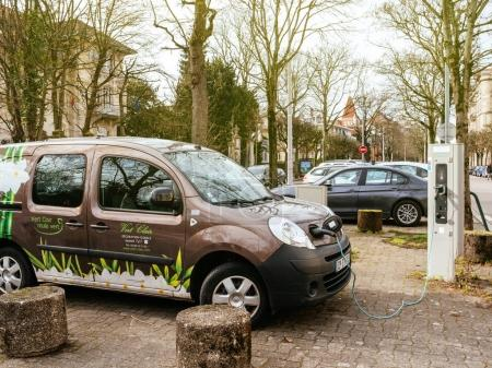 Plugged in Renault mini-van electric car on the street electric