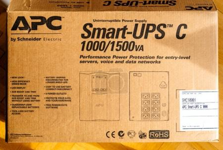 PARIS, FRANCE - MAR 29, 2018: Cardboard unboxing of APC Smart-UPS C 1000VA LCD 230V enterprise-level uninterruptible power supplies made by American Power Conversion on office wooden floor