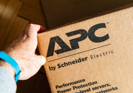 PARIS, FRANCE - MAR 29, 2018: man holding hand near the logo of APC Smart-UPS C enterprise-level uninterruptible power supplies made by American Power Conversion Schneider Electric