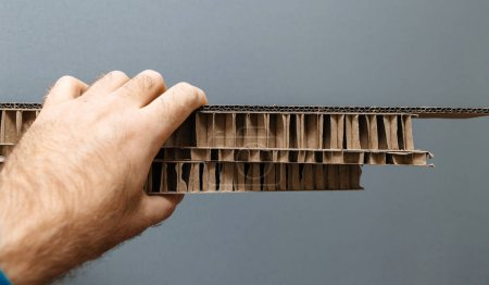 Factory worker male hand holding and inspecting against gray background a stack of multiple thickness corrugated cardboard carton paper for packing