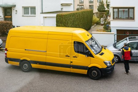 Photo for PARIS, FRANCE - MAR 30, 2018: Courier enters DHL yellow delivery van after delivering the on time delivering package parcel in typical European neighborhood - elevated view - Royalty Free Image