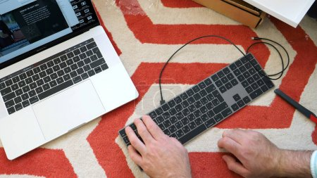 Photo for LONDON, UNITED KINGDOM - APR 15, 2018: Man unboxing installing charging connecting to Apple MacBook pro retina laptop 15 inch to new Magic Keyboard with Numeric Keypad Space Gray - Royalty Free Image
