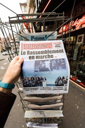 POV man holding Present newspaper with Marine Le Pen