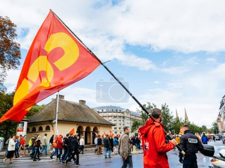 Photo for STRASBOURG, FRANCE - SEP 12, 2018: Central street with man waving CGT flag on street during a French Nationwide day of protest against labor reform proposed by Emmanuel Macron Government with police - Royalty Free Image
