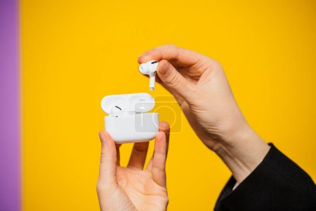 Photo for Paris, France - Oct 30, 2019: Woman hands unboxing new Apple Computers AirPods Pro headphones with Active Noise Cancellation for immersive sound - charging case yellow background - Royalty Free Image