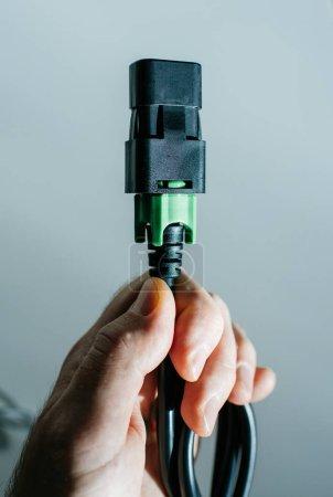 Photo pour Homme tenant main un câble d'alimentation Iec noir et vert sur fond bleu - image libre de droit