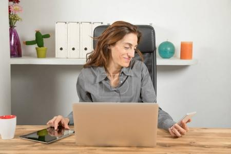 multitasking businesswoman with phone tablet and computer