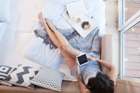 Photo for Young beautiful brunette woman with tablet sitting down on the bed by the window. Top view from above. Lazy day off concept - Royalty Free Image