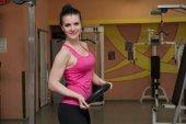 Krásná dívka stojí s sportovního vybavení ve fitness klubu