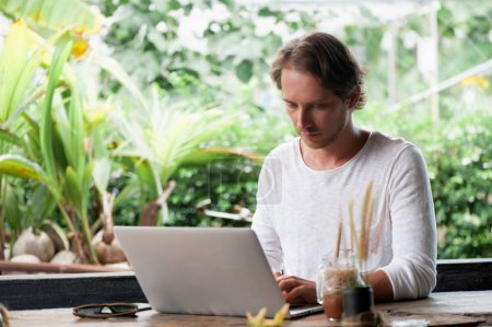 Photo for Young male freelancer sitting in outdoor cafe working in laptop - Royalty Free Image