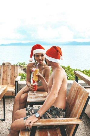 Photo pour Joyeux couple assis à la table avec des cocktails et souriant à la plage - image libre de droit