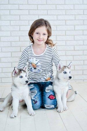Happy girl and Husky puppies lying on white floor