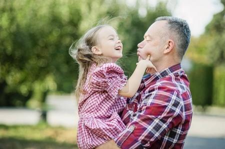 Photo pour Grand-père tenant sa petite-fille dans un parc vert d'été. Je t'aime tellement mon grand-père. Grand-père embrasser petit-enfant - image libre de droit