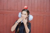 Portrait of a schoolgirl standing with apple on head