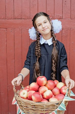 Portrait of a schoolgirl standing with apple on head