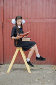 schoolgirl with books sitting on a yellow staircase
