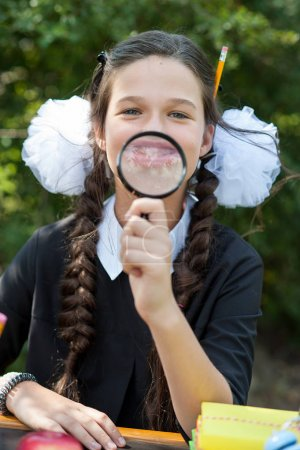 Portrait of a beautiful young Schoolgirl looking through a magnifying glass and sitting at a desk