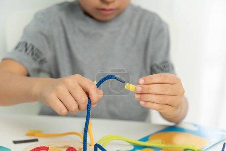 Photo pour Développement de la motricité fine. Éducation précoce, méthode Montessori. Capacités cognitives, Développement de l'enfant. Gros plan des mains d'enfants jouant avec de la dentelle ou de la corde et des pâtes alimentaires - image libre de droit