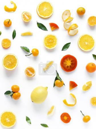 Creative flat layout of fruit, top view. Sliced oranges, lemon, persimmon, tangerine, green leaves isolated on white background. Food wallpaper, composition pattern of fresh fruits