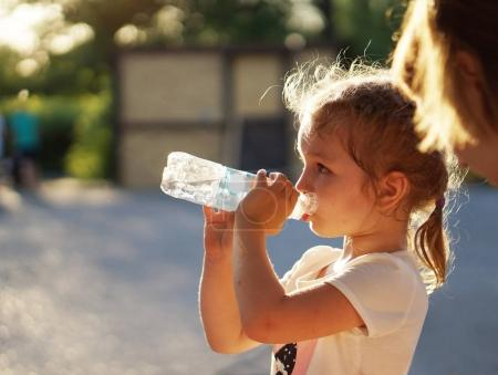 Blonde preschooler girl drinking water out of bottle in yard