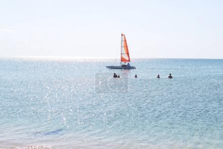red sailing canoe on sea, people swimming in sea