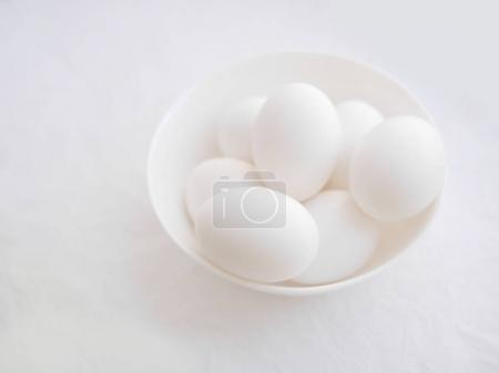 Close view of eggs in bowl on white background